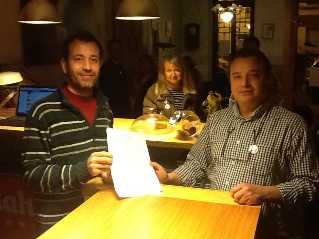 David, el titular del local, entrega a Emilio Verdú una hoja de firmas