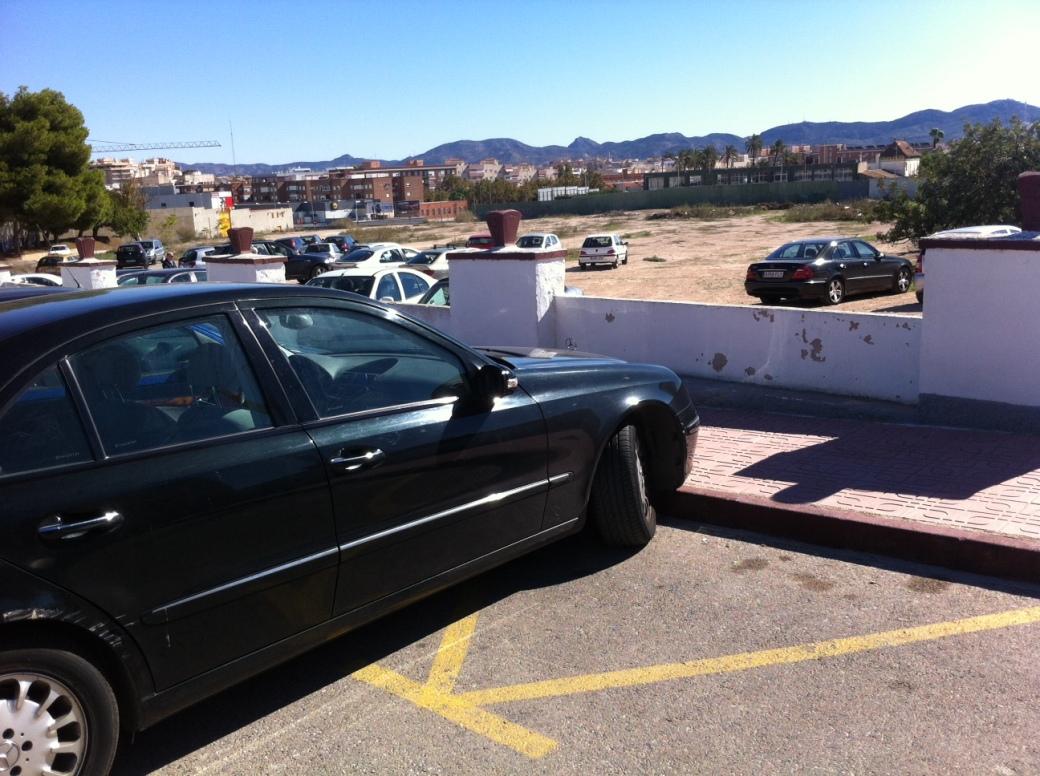 Vehículo mal estacionado junto a descampado vacío